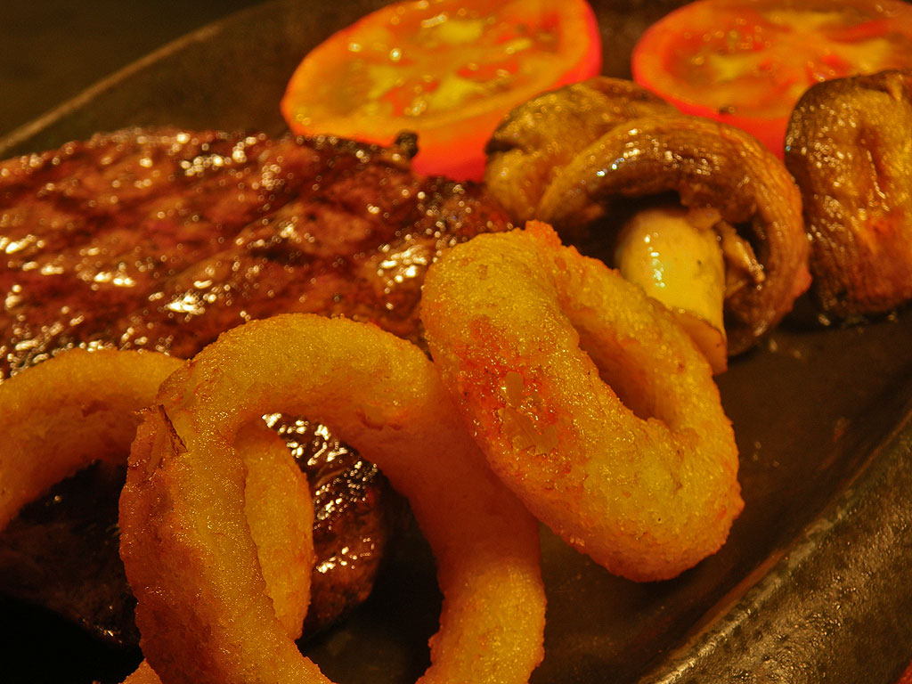 Steak cooked to your liking, with onion rings, tomatoes and mushrooms
